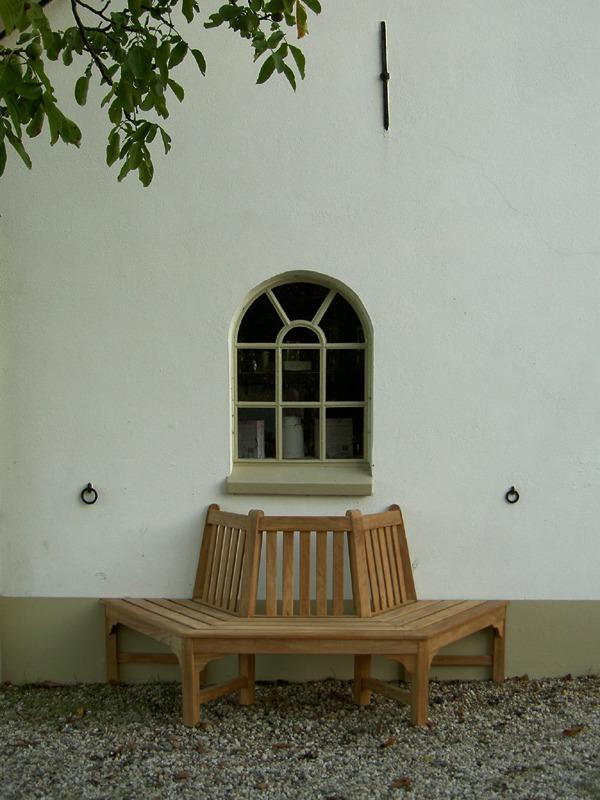 halve boombank van teakhout tegen muur