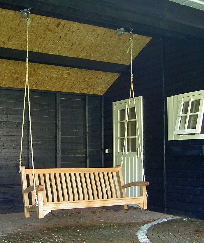 schommelbank van hout met touwen onder veranda