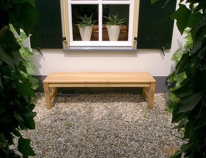 tuinbank van hout zonder rugleuning onder raam