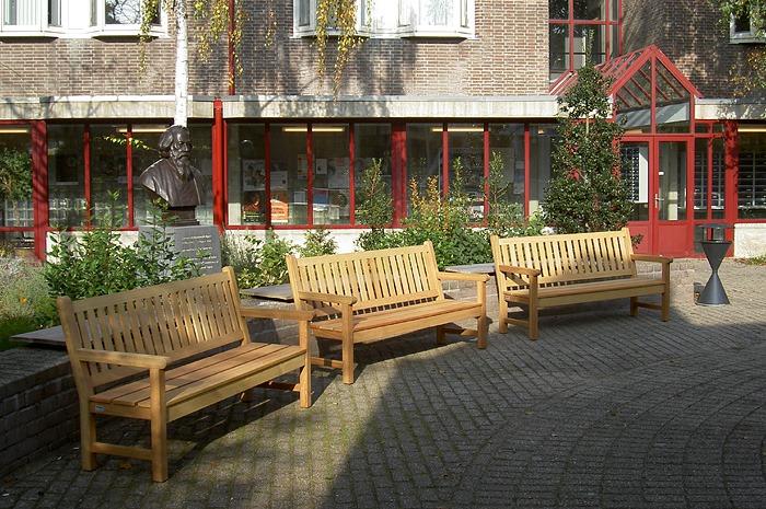 houten tuinbanken van vondel tuinmeubelen in tuin bij universiteit in Leiden